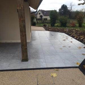 Aménagement d'une terrasse en dalle et béton désactivé avec des pavés noir par l'entreprise Cuinet de Tarcenay