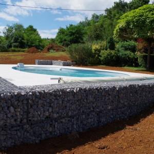 dallage autour d'une piscine en dalle EVO2, y compris coupe de margelle avec les dalles en grès céram et mur de soutien en gabion réalisé par l'entreprise Cuinet de Tarcenay vers Besançon dans le Doubs