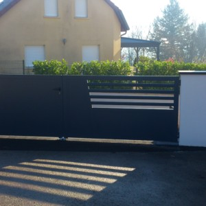 maçonnerie pour portail réalisé avec des murs en blocs coffreurs recouverts de couvertines et crépis, avec un seuil en pavés type Kronimus Harmonie gris anthracite réalisé par l'entreprise CUINET basée à Tarcenay vers Besançon dans le Doubs